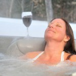 Woman in an outdoor hottub  with her head back with a glass of wine next to her. Steam is rising from the tub.  Snow is on the ground with trees in the background.